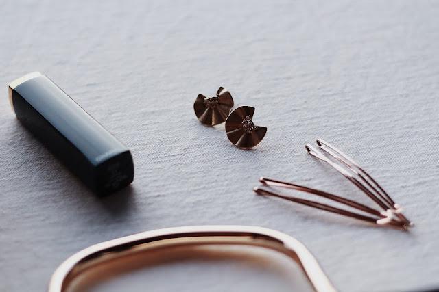 Złote dodatki na stylizacji - wsuwki do włosów, kolczyki, torebka oraz pomadka Chanel.