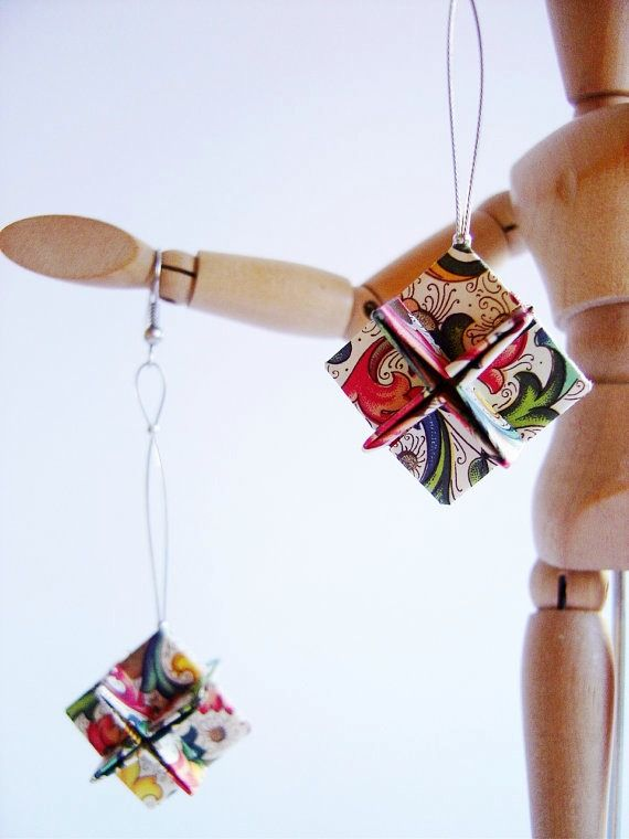 folded paper cube-shape earrings displayed on arm of wooden figure