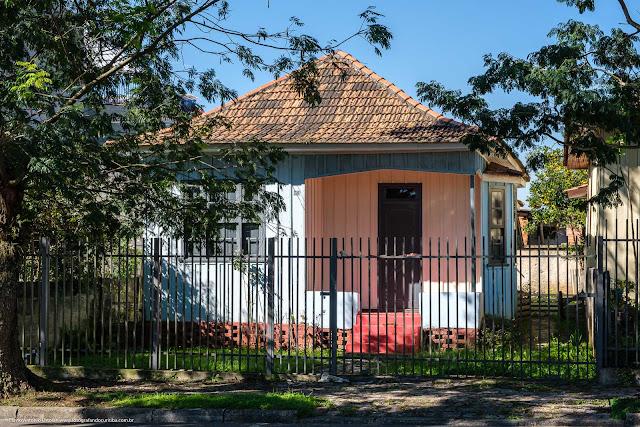 Casa de madeira pintada de azul e rosa