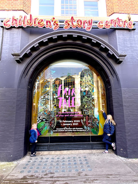 2 children posing either side of a window display for Fairy Tales with the children's story centre  written in neon lights above it
