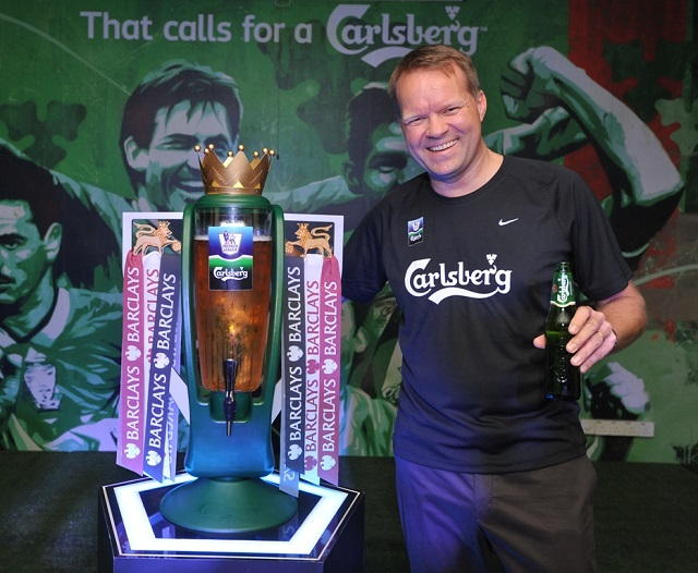"Henrik Andersen, Managing Director of Carlsberg Malaysia, with the custom-made Barclays Premier League ""Beer Tower"" Trophy at his side and the replica of the Liverpool Legends mural  in the background"