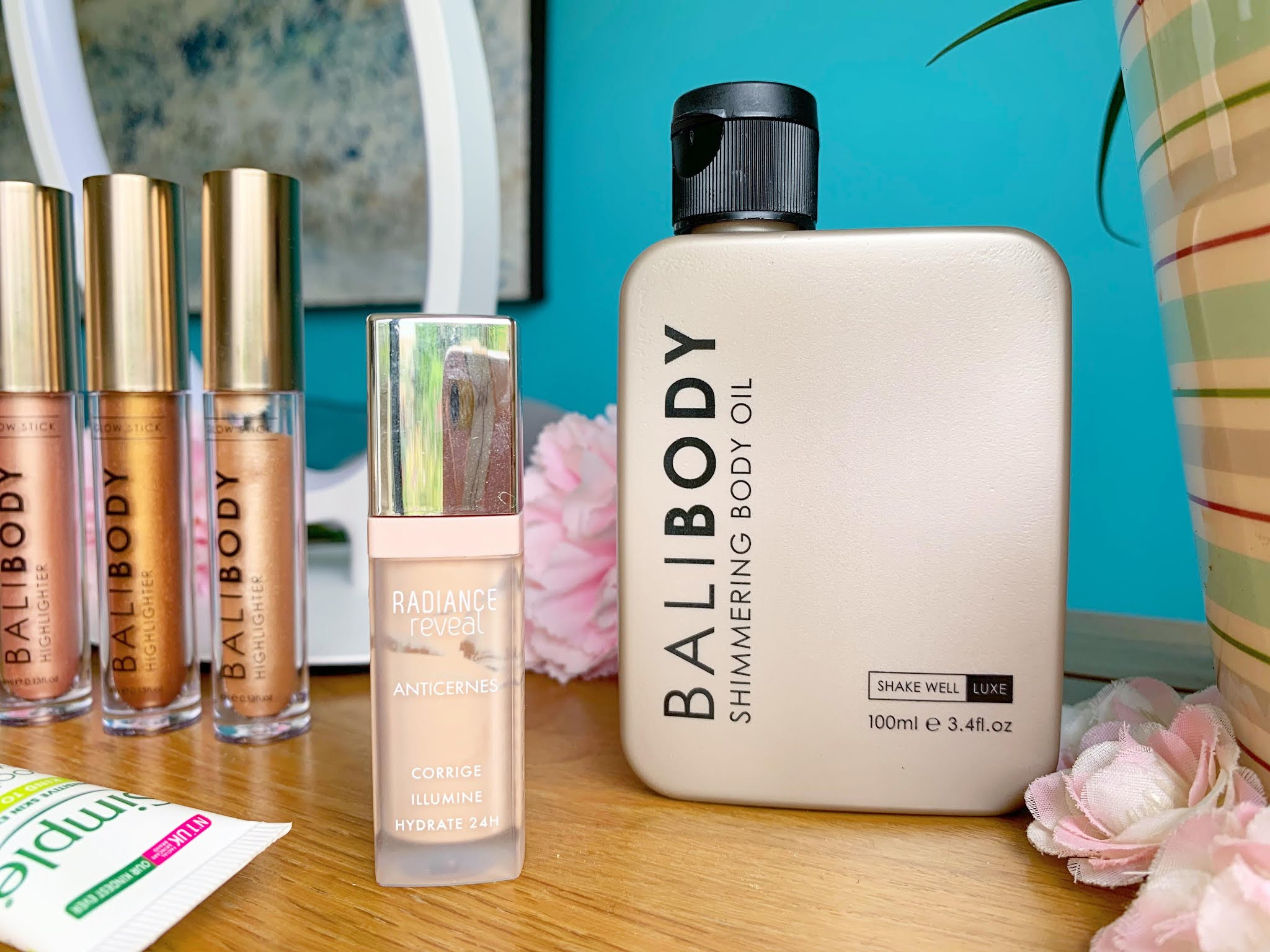 Bali Body Shimmering Body Oil and Bourjois Radiance Concealer on a side table with a blue background