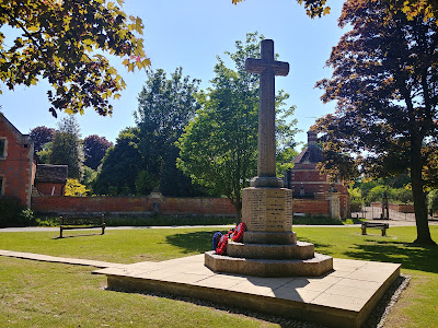 Photograph of the north side of the war memorial with the Octagon Lodge of North Mymms Park in the background. Image by the North Mymms History Project released under Creative Commons