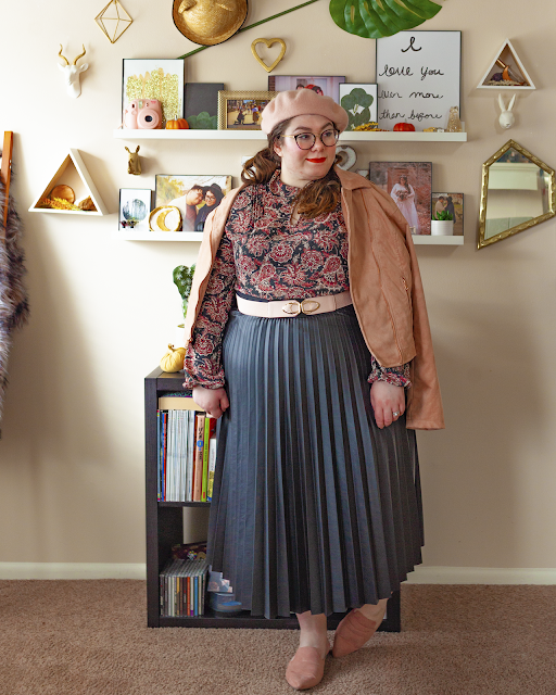 An outfit consisting of a pastel pink beret, a rose gold pink suede moto jacket draped over the shoulders, a pink and black paisley peter pan collared dress worn as a top, tucked into a pleated black faux leather midi skirt and muted pink pointed toe mules.