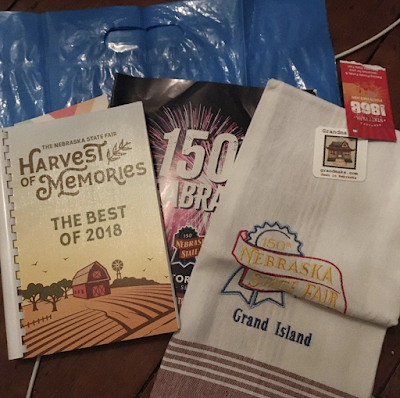 a pile of items from the Nebraska state fair, including a tea towel and cookbook