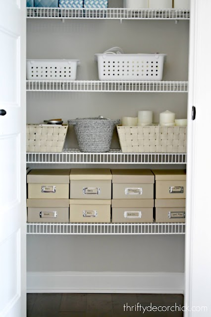 organized linen closet with photo boxes