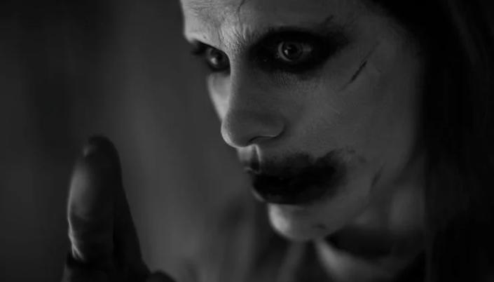 Imagem: foto em preto e branco mais próxima do rosto do novo visual do Coringa, com um rosto branco, a maquiagem ao redor dos olhos e boca borrada, cabelos escuros e compridos e erguendo um dedo enluvado.