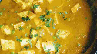 Cooking matar paneer with chopped coriander leaves