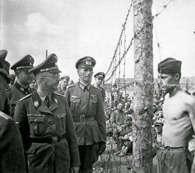 Himmler, acompañado de soldados frente a un prisionero en el campo de concentración nazi
