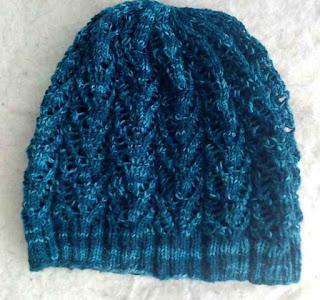 A lace hat knit in dark green fingering-weight yarn.