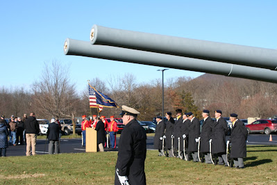 Men in military uniform gathered for tribute ceremony under two long gray battleship guns. A podium flanked by flags is in the background.