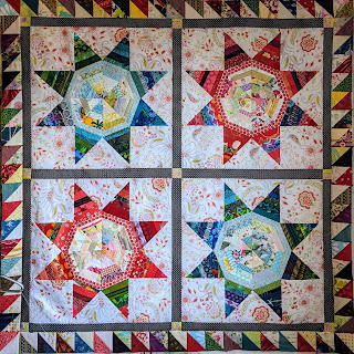 """3"""" HSTs in red, blue, brown, and black prints paired with cream and yellowish lights form the first border around the LeMoyne Stars in the quilt"""