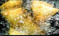 Deep frying onion samosas in hot oil