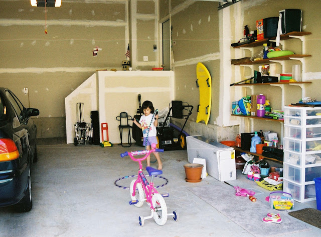 little girls playing in garage with a little bike and toys