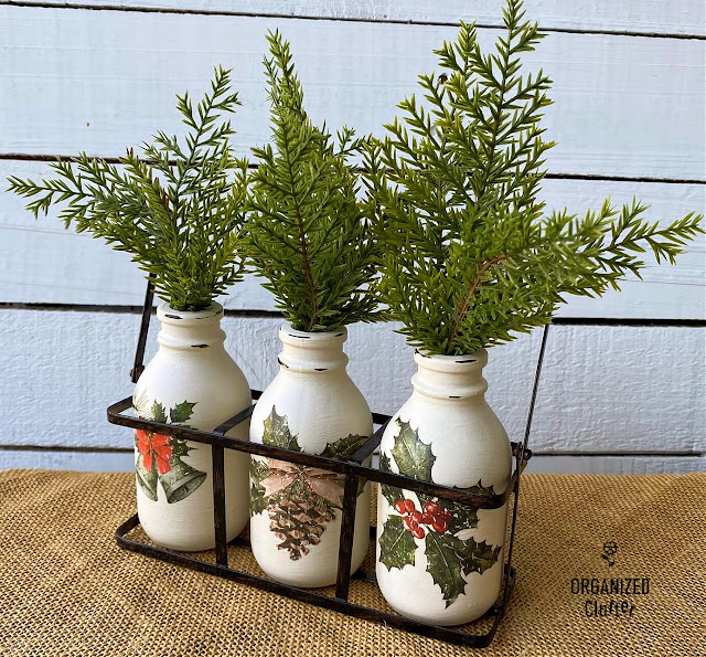 Photo of three chalk painted garage sale bottles with Christmas decor transfers and greenery in a wire holder.