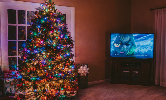 A Christmas tree next to a TV