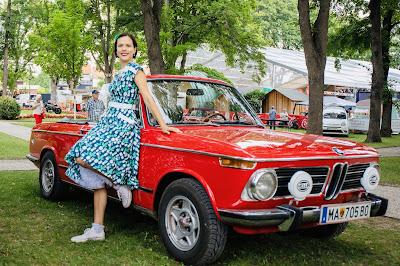 maria gamauf vom utsc dancefire in einem kleid von boutique new vintage an einem roten oldtimer lehnend bei rocknroll im kurpark Bad Sauerbrunn