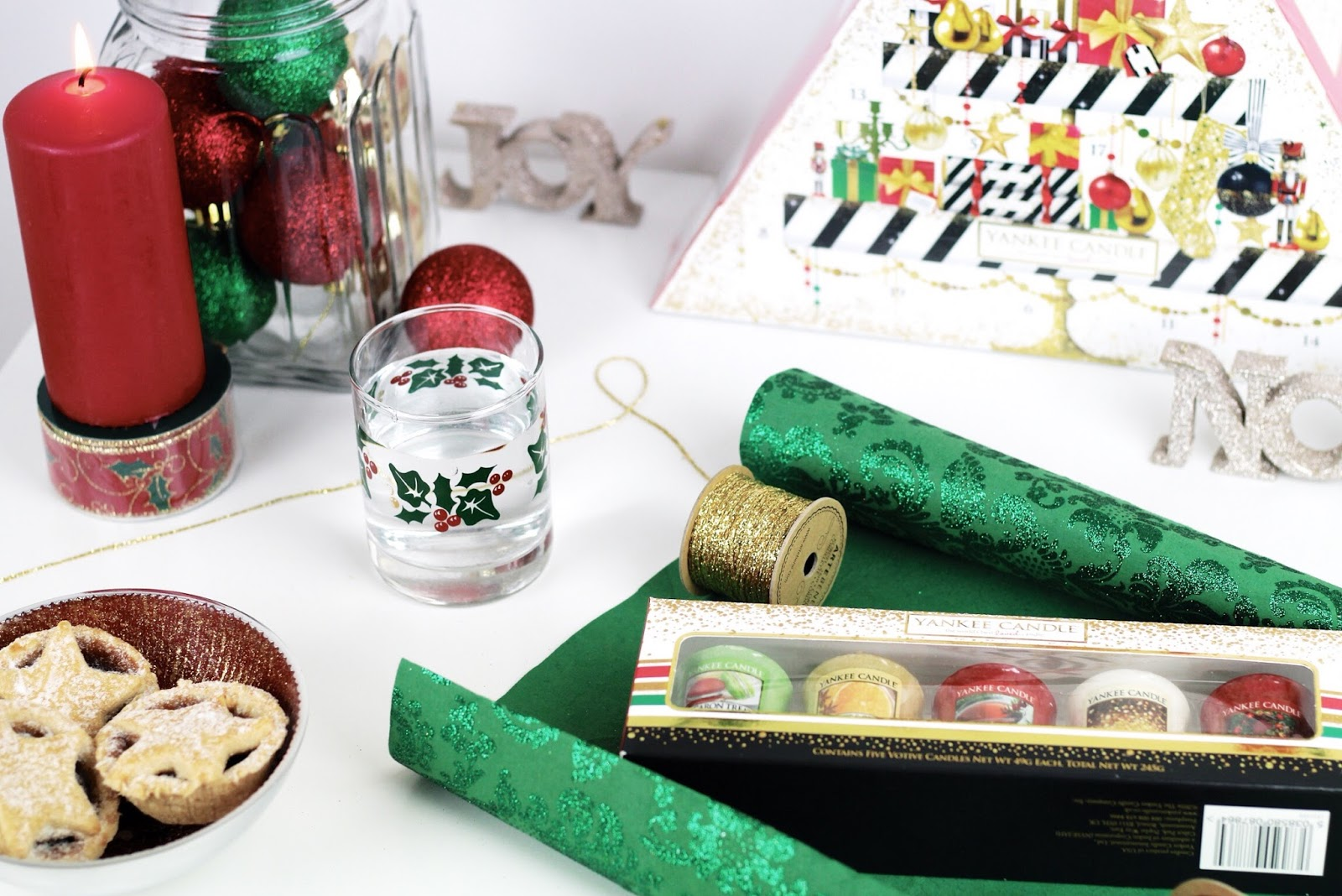 Red and green Christmas gift wrapping scene with candles