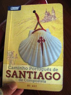 mão segurando um guia do Caminho Portuguêse de Santiago