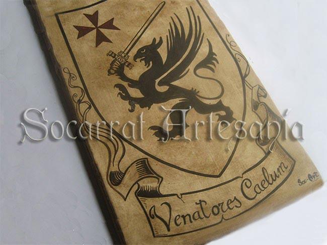 Escudo con los atributos personalizados: Cruz de Malta, Grifo con espada, y nombre en latín. Socarrat Artesanía. Soc-Art. Camateu