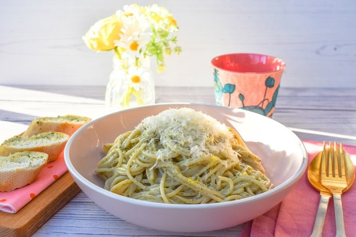 Close up of pasta bowl piled with Creamy Lemon Basil Spaghetti topped with grated parmesan