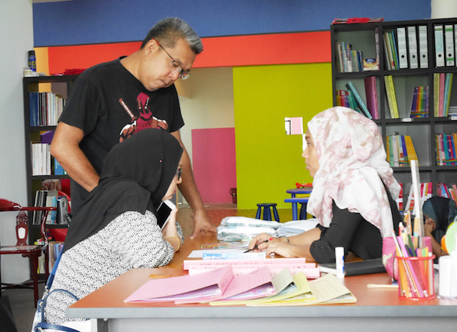 Cikgu Sham consulting the new parents who walked in to enquire