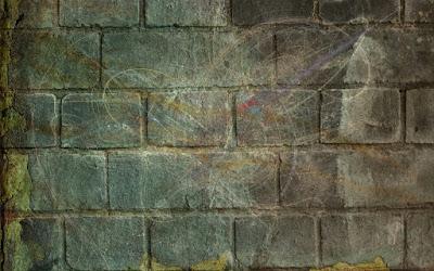 A brick wall with graffiti scrawled on it.
