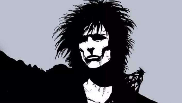 Imagem: o personagem Morfeus de Sandman, um homem pálido, em vestes pretas, os cabelos pretos longos e bagunçados, o rosto muito pálido e os olhos completamente pretos.