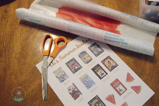 Use the squares on the back of the contact paper to measure the book covers and cut a scratch-off sticker that fits.