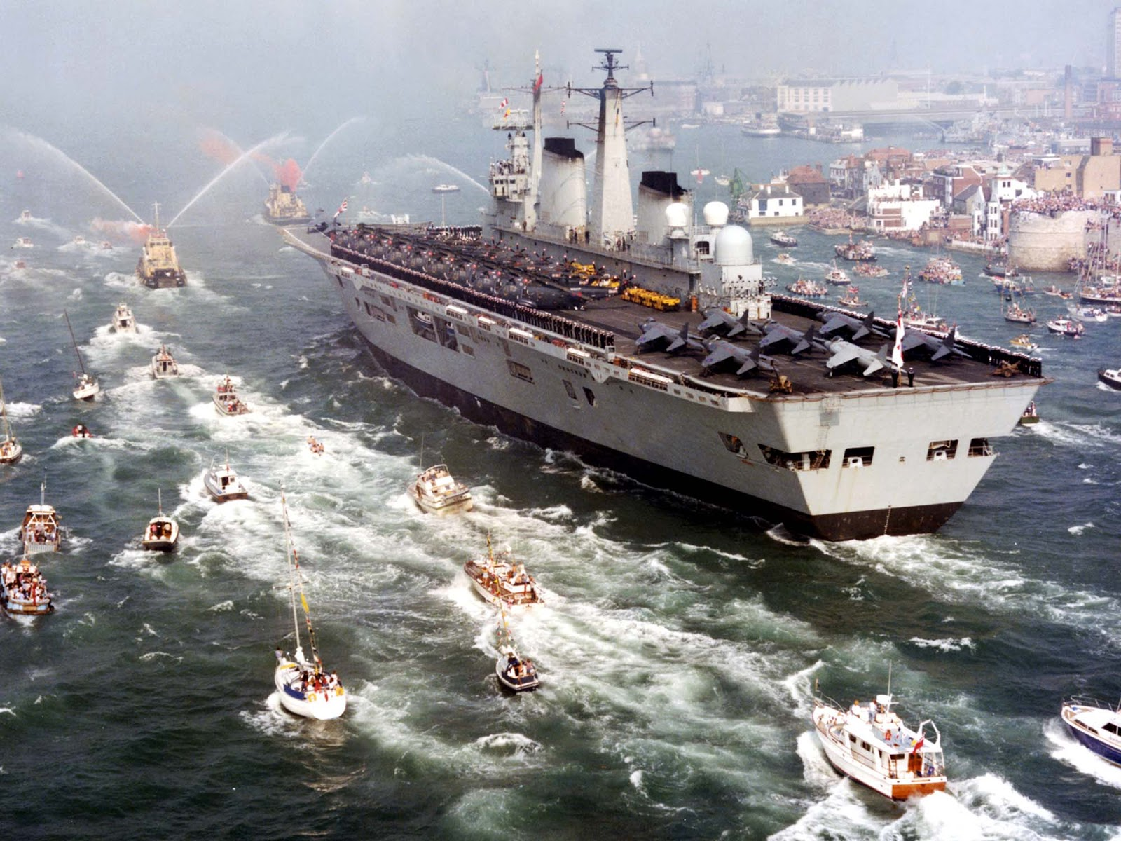 HMS Invincible returns to massive celebrations following the Falklandís Conflict in 1982. Lined up on deck are Sea King helicopters from 820 Naval Air Squadron and Sea Harrier FRS1 aircraft from 800 Naval Air Squadron.