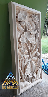 Gambar relief tempelan dinding motif sembilan ikan koi dengan variasi bunga lotus yang dibuat dari batu alam paras jogja atau batu putih gunungkidul