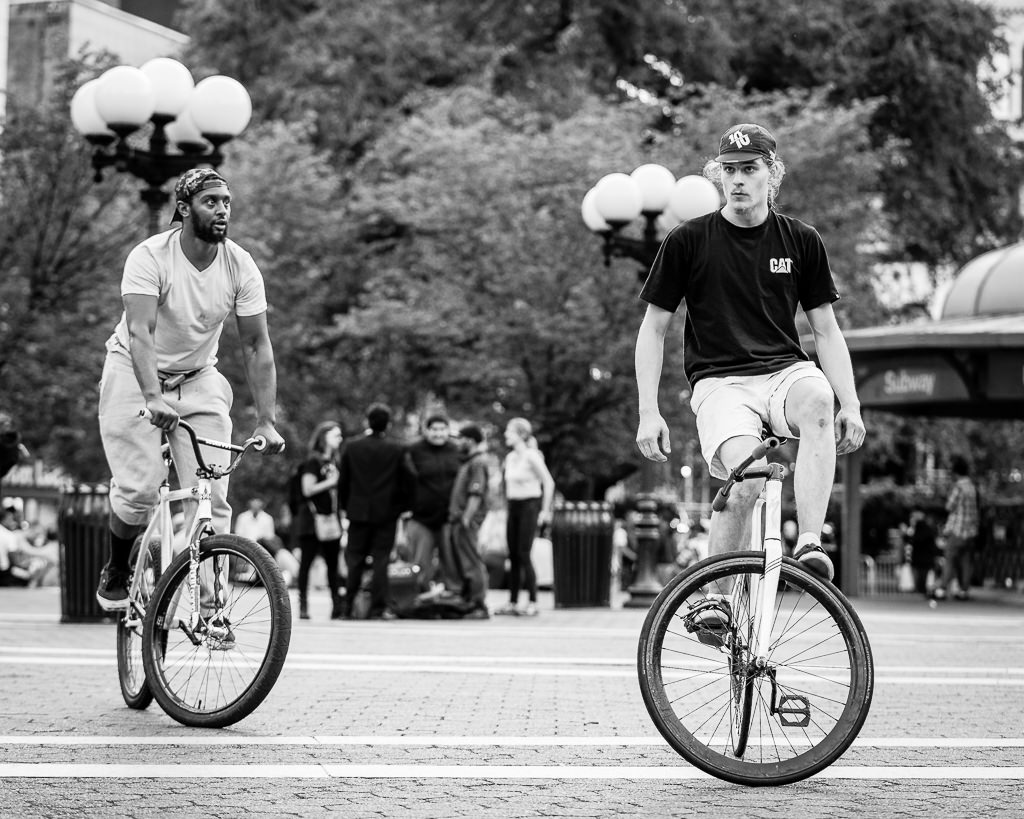 a photo in black and white of two men performing stunts on bicycles in union square park