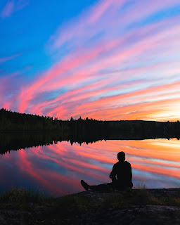 person silhouette sitting looking at a blue and pink sunset or sunrise
