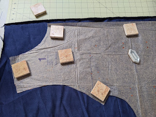 Pattern laid out on fabric with weights on pattern