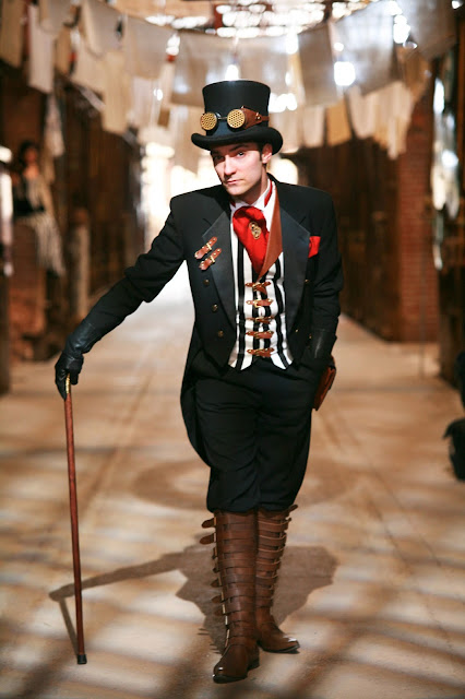 Man dressed in steampunk clothing: top hat, goggles, waistcoat, ascot, tailcoat, boots, cane. Steampunk fashion and costumes for men.
