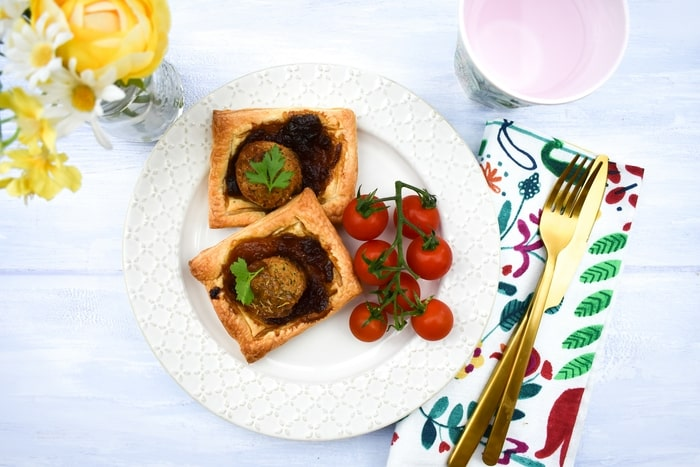 cold falafel pie with cherry tomatoes next to yellow spring flowers