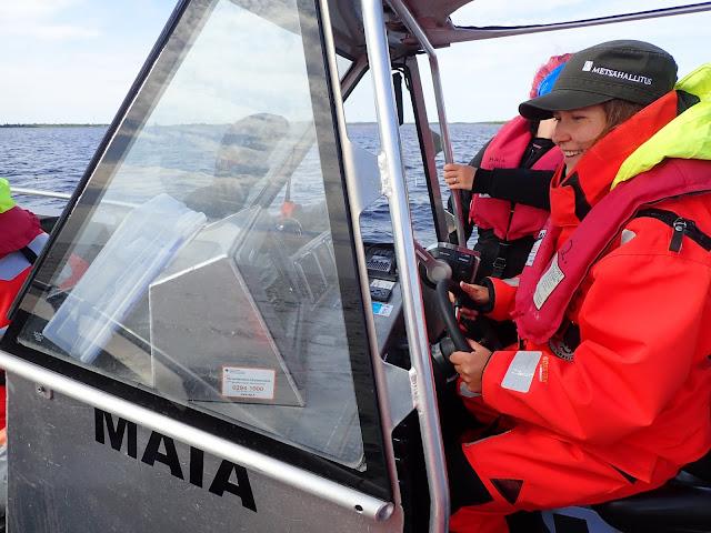 Työntekijä ajaa Maia venettä hymyssä suin.