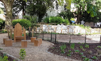 Outdoor feature including wooden chairs and rockery