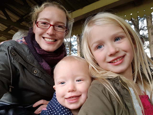 Me, Little and Big Sister sitting on a miniature train pulling cheesy grins for the camera
