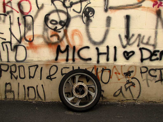 Lone scooter wheel, with perforated brake disc, lost against a wall with graffiti, Livorno