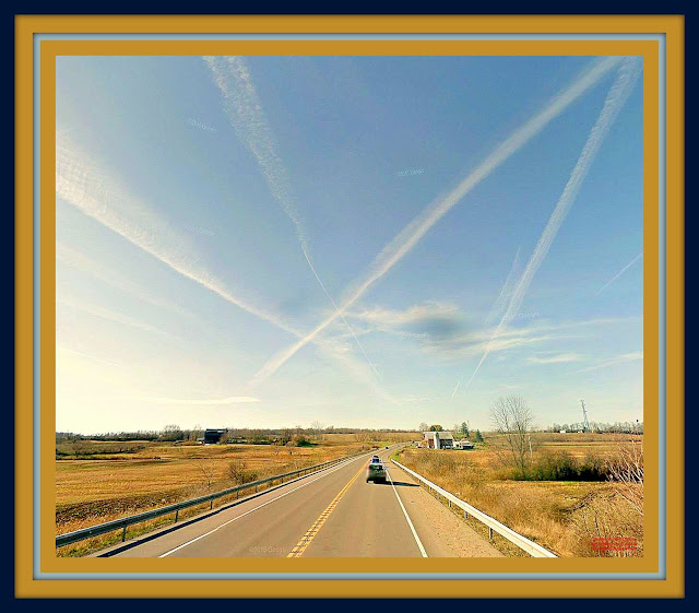 jet contrails streak sky as road disppears in distance between two barns
