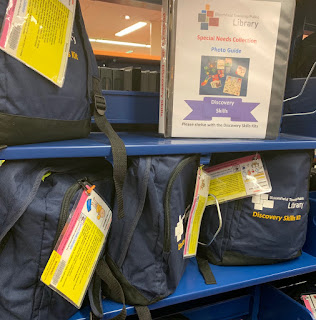 two shelves of blue Discovery Skills Kit backpacks and photo guide