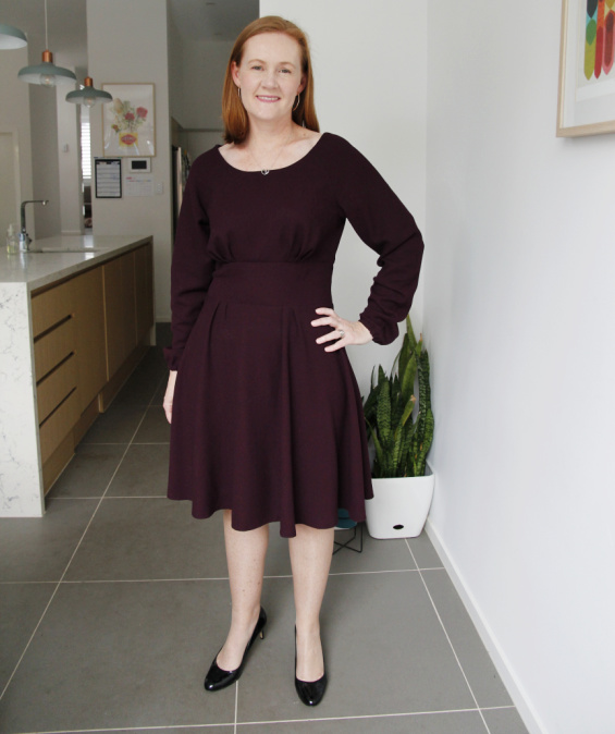 a white woman posing in a maroon dress