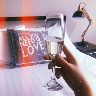 my hand holding a glass of prosecco with a cushion in the background that says all you need is love