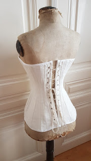 back/side view of the edwardian corset on an edwardian dress form