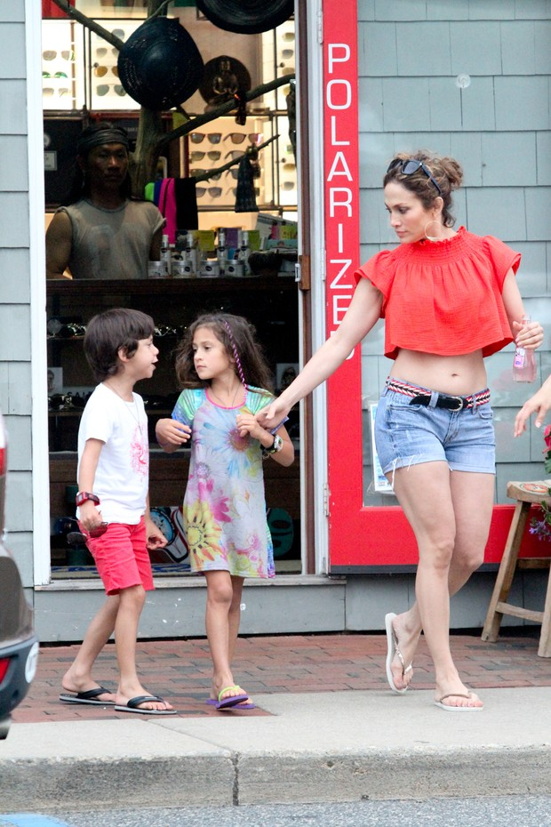 Shorts and belly out, Jennifer Lopez walks with children