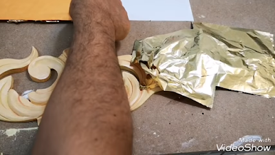 تطبيق ورق الذهب برفق بواسطة اليد على سطح وحدة خشبية نباتية