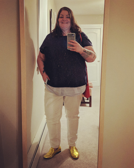 image of me in a full-length mirror wearing a navy blue top, white jeans, and gold shoes, while carrying a red purse