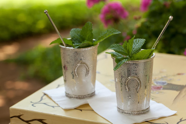 two silver julep cup with mint sprigs in them sitting on a metal table