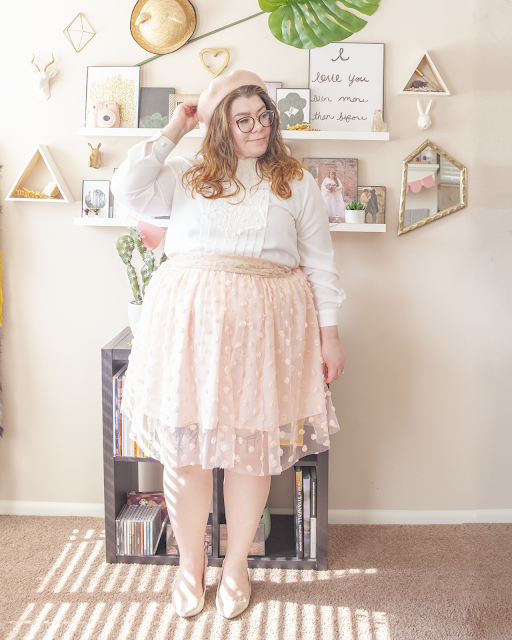 An outfit consisting of a pastel pink beret, a vintage white blouse with a lace and pleats front, tucked into a pastel pink knee length skirt with rosettes, and beige slingback heels.